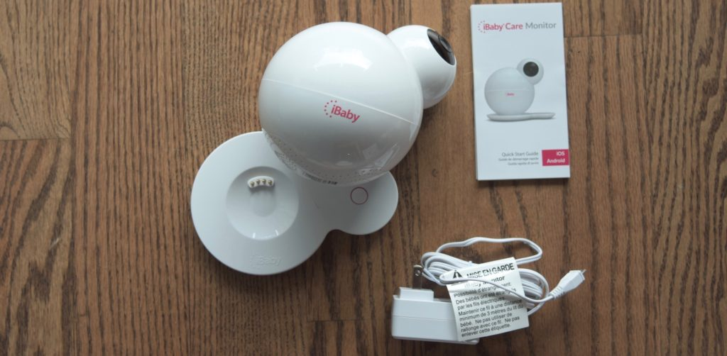 The iBaby M6S, its base, quick start guide and power cord on a hardwood floor