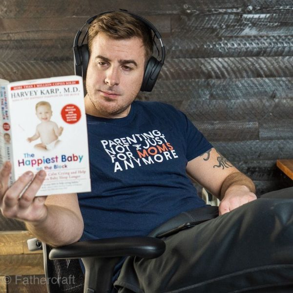 A guy reading a book with headphones wearing a parenting, not just for moms anymore t-shirt