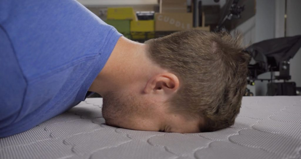 A guy with his face in the Newton Crib Mattress